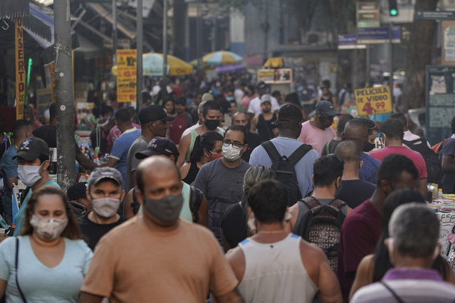 Pedestrians, some wearing protective face masks, walk through a street market in downtown in Rio de Janeiro, Brazil, Thursday, June 25, 2020. Rio continues with its plan to ease restrictive measures due to the new coronavirus and open up the economy to avoid an even worse economic crisis. (Photo by Leo Correa/AP Photo)