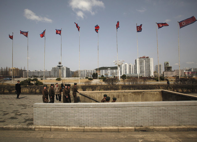 Soldiers walk into a subway in front of a column of North Korean flags in Pyongyang, April 11, 2012. (Photo by Bobby Yip/Reuters)