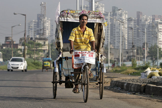 Satyen Das rides his rickshaw on a road in Kolkata, India, Thursday, October 9, 2014. It took 68 days for Das to laboriously pedal his rickety, self-remodeled bicycle rickshaw from the seaside Indian city of Kolkata to the roof of the world – a 5,369-meter (17,600-foot) Himalayan peak. His goal: to promote his chassis as an environmentally sound travel option. (Photo by Bikas Das/AP Photo)