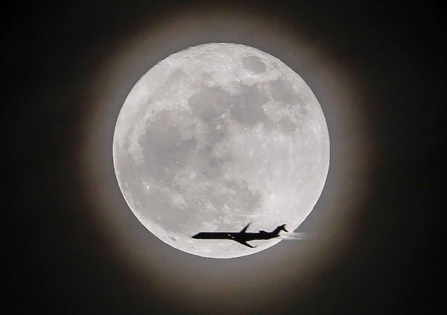 An airplane crosses in front of the moon, a so-called supermoon, in Avondale Estates, Georgia, USA, 03 December 2017. (Photo by Erik S. Lesser/EPA/EFE)