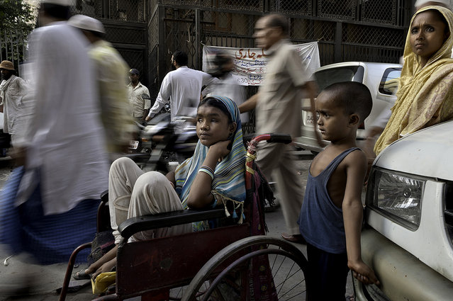 A sea of people passes by Hunupa Begum, 13, who has been blind for the past 10 years and lives close to the Nizamudin Bangala Masjid (Mosque) in New Delhi, India. She begs as the only source of income for her family that consist of a brother Hajimudin Sheikh, 6, center, who suffers fluids that accumulate in his head and her mother Manora Begum, 35, right, who suffers from Asthma, and she has a womb ailment and can't do manual labor. Their father Nizam Ali Sheikh died ten years ago of Tuberculosis. Her wheelchair was donated by a passerby. (Photo by Renée C. Byer/Living on a Dollar a Day)