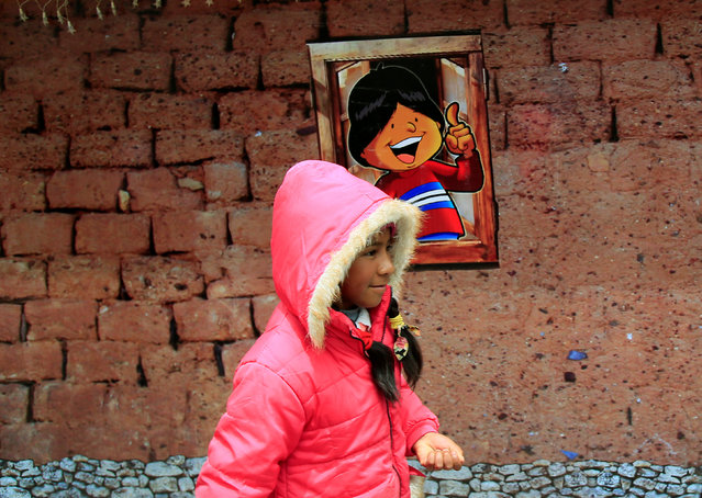 """A girl walks pass the facade of a replica of the house where Bolivia's President Evo Morales was born, as it is presented by the government as """"The House of Desires"""", during the Christmas season at the Murillo square in La Paz, Bolivia, December 8, 2017. (Photo by David Mercado/Reuters)"""