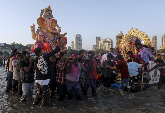 Devotees carry idols of Hindu elephant god Ganesh, the deity of prosperity, for immersion into the Arabian Sea on the last day of the Ganesh Chaturthi festival in Mumbai, India, September 27, 2015. (Photo by Danish Siddiqui/Reuters)