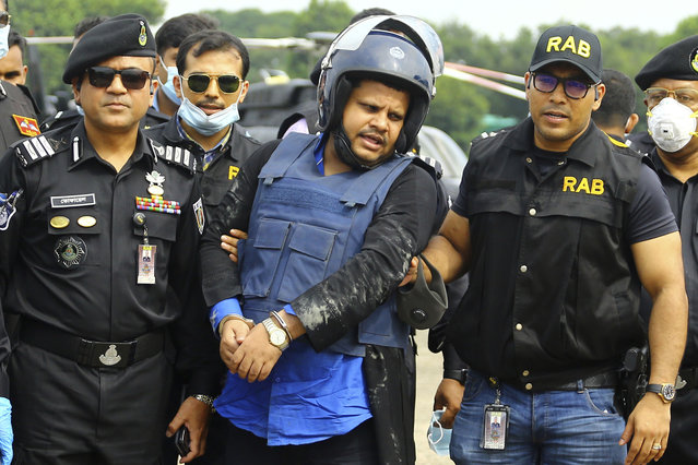 Mohammed Shahed, center, the owner of two hospitals that issued thousands of fake coronavirus test reports is brought by helicopter after being arrested by Bangladesh's Rapid Action Battalion personnel in Dhaka, Bangladesh, Wednesday July 15, 2020. Shahed, a member of the governing party who regularly appeared on TV talk shows, was arrested Wednesday near the Indian border as he attempted to flee the country to India. (Photo by Sourav Lasker/AP Photo)