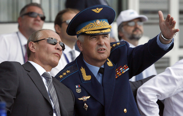 Russia's Prime Minister Vladimir Putin listens to Air Forces' Commander-in-Chief Alexander Zelenin as they watch planes performing during the opening of the MAKS-2009 international air show in Zhukovsky outside Moscow, August 18, 2009. (Photo by Sergei Karpukhin/Reuters)
