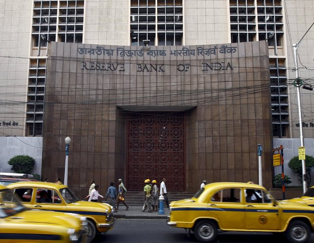 Commuters travel past a Reserve Bank of India (RBI) building in Kolkata in this November 11, 2014 file photo. Though the Reserve Bank of India is expected to cut interest rates next week by a quarter percent to a four-year low, officials say concerns over prices make it likely to resist political pressure for significant easing in the coming months. (Photo by Rupak De Chowdhuri/Reuters)