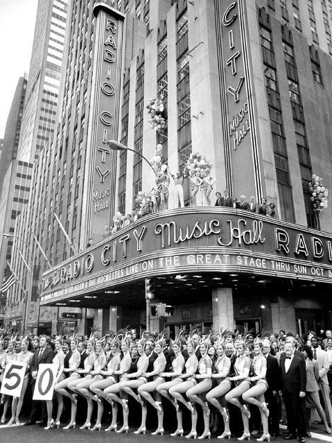 The Radio City Music Hall Rockettes dance on Sixth Avenue in New York City on Saturday, October 2, 1982 in a celebration of the music hall's 50th anniversary.  Standing atop the marquee, at center, is singer Peter Allen. (Photo by W. Jorgensen/AP Photo)