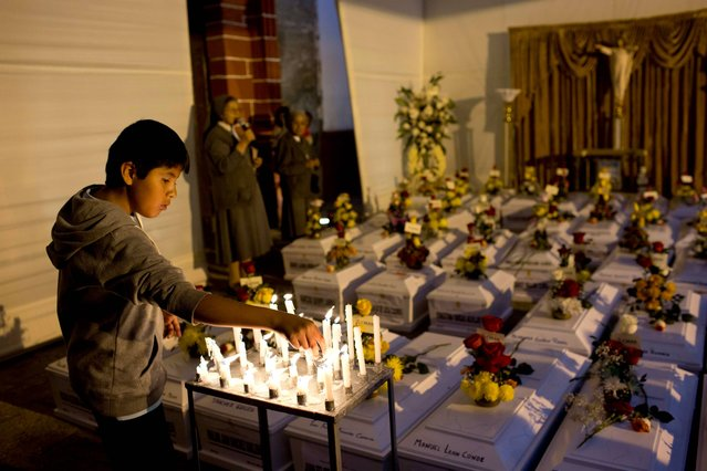 A boy lights a candle before a mass with the coffins containing exhumed remains of the country's dirty war victims, in La Compania de Jesus Church in Huamanga, Peru, Monday, October 27, 2014. Hundreds arrived in the Ayacucho state capital for Monday's handover of 80 sets of remains. Simple white coffins bore the bones of fathers, mothers, wives, children and brothers sslain three decades ago during Peru's dirty war. (Photo by Rodrigo Abd/AP Photo)