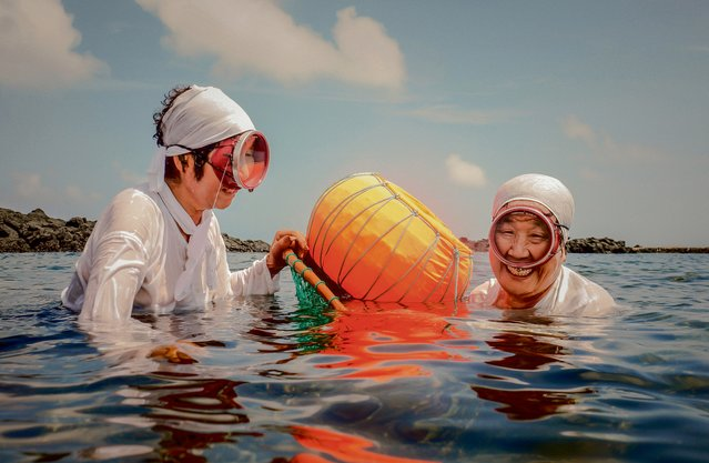 Ja Kang Song, 71, and Ja Hyun Su, 72, dive for shellfish and are the main breadwinners for their families. In South Korea, 45% of the diving women of Jeju are over the age of 70. Routinely diving to depths of 20m and staying under for an average of two to three minutes, the pressure on the body takes its toll and, like many others, burst eardrums have left Ja Hyun Su deaf. Each season, between seven and 10 women die diving the waters around Jeju Island. (Photo by Andy W. Langton/Age International)