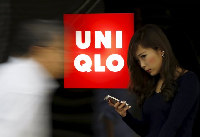 A woman holding her mobile phone stands next to a logo of Fast Retailing's Uniqlo outside its store in Tokyo in this October 7, 2014 file photo. Japan's Fast Retailing Co Ltd missed its own forecasts and reported on October 8, 2015 a 26 percent rise in annual operating profit, saying it had booked impairment losses related to its J-Brand label and some U.S. stores of its Uniqlo brand. (Photo by Yuya Shino/Reuters)