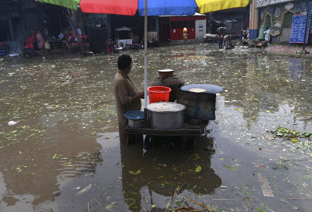 A food vendor waits of customers in a flooded area after heavy monsoon rains in Lahore on August 10, 2020. (Photo by Arif Ali/AFP Photo)