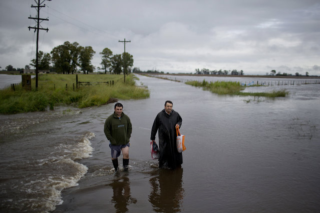 Men wade through flooded roads near Carmen de Areco, Argentina, Monday, November 3, 2014. Two people have died due to the heavy rain that started Thursday, affecting the province of Buenos Aires where thousands have evacuated their homes. (Photo by Natacha Pisarenko/AP Photo)