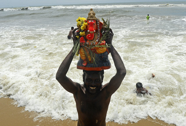 A volunteer carries a clay idol of Hindu elephant-headed deity Ganesh for immersion on the third day of the Ganesh Chaturthi festival, in Chennai on August 24, 2020. India's much-loved Ganesha festival opened to a muted reception on August 22 as tough COVID-19 coronavirus restrictions prevented devotees from holding grand celebrations and carrying out traditional rituals to honour the Hindu elephant god. (Photo by Arun Sankar/AFP Photo)