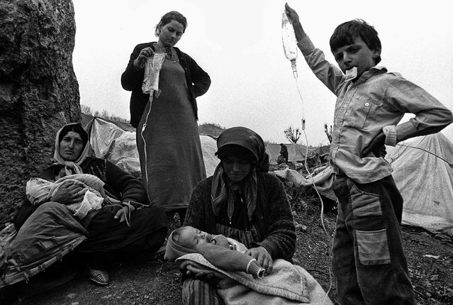 "Iraqi Kurdish refugees wait with children in Cukurca refugee camp in Turkey April 8, 1991. Reuters photographers have chronicled Kurdish refugee crises over the years. In 1991 Srdjan Zivulovic documented refugees in Cukurca who had escaped a military operation by Saddam Hussein's government in Iraq aimed at ""Arabising"" Kurdish areas in the north. (Photo by Srdjan Zivulovic/Reuters)"