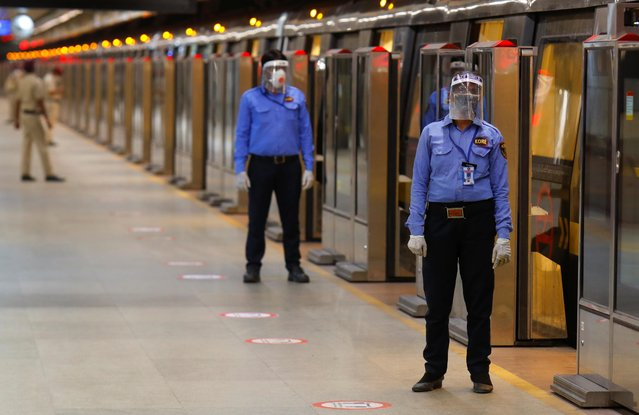 Security guards wearing face masks and shields stand on a Delhi metro train platform, on the first day of the restart of their operations, amidst the spread of coronavirus disease (COVID-19), in New Delhi, India, September 7, 2020. (Photo by Adnan Abidi/Reuters)