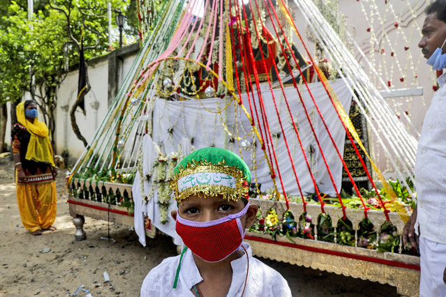 A Muslim boy wearing face mask stands in front of a replica of the highest seat of Imam Hussain, the great grandson of Prophet Muhammad prior to a Muharram procession in Kolkata, India, Sunday, August 30, 2020. India has the third-highest coronavirus caseload after the United States and Brazil, and the fourth-highest death toll in the world. (Photo by Bikas Das/AP Photo)