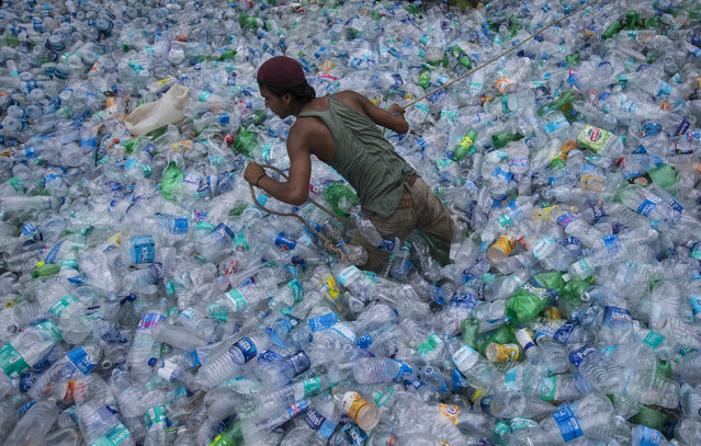 A worker uses a rope to move through a pile of empty plastic bottles at a recycling workshop in Mumbai June 5, 2014. (Photo by Danish Siddiqui/Reuters)