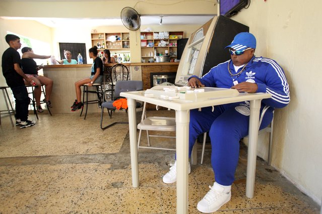 The dead body of Jomar Aguayo is seated at a table with domino tiles in San Juan, October 19, 2015. (Photo by Alvin Baez/Reuters)