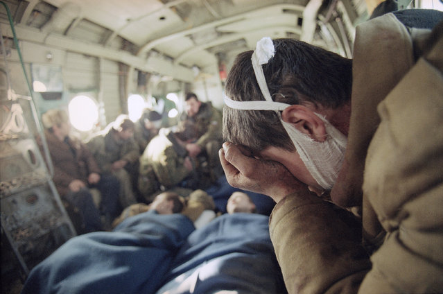 A wounded Russian soldier, who has been evacuated with his comrades, weeps in a helicopter on his way out of Grozny on Friday, February 3, 1995, as the fighting in the Chechen capital continues. The massive Russian force that invaded Chechnya has taken very heavy losses against a small but determined guerrilla force. (Photo by Karsten Thielker/AP Photo/File)