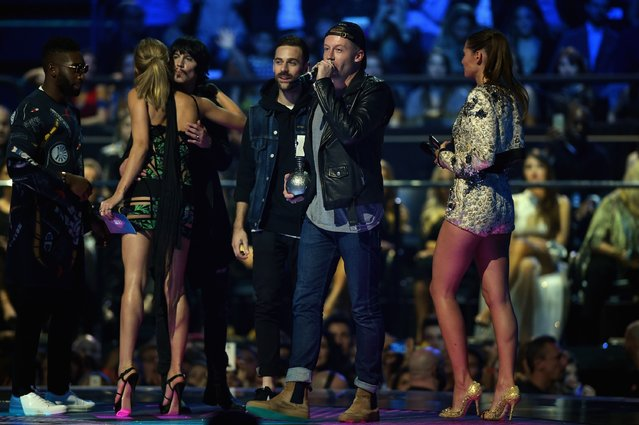 (L-R) Eric Nally (3rd-L), Ryan Lewis (3rd-R) and Macklemore (2nd-R) accept the award for Best Video for ''Downtown'' from Bianca Balti (R), Tinie Tempah (L) and Hailey Baldwin (2nd-L) on stage during the MTV EMA's 2015 at the Mediolanum Forum on October 25, 2015 in Milan, Italy. (Photo by Brian Rasic/Getty Images for MTV)