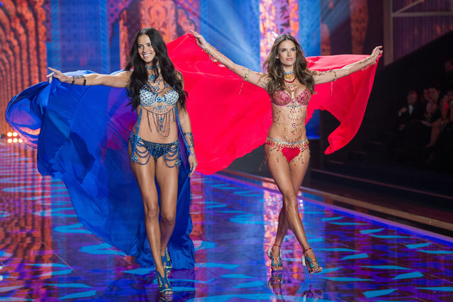 Models Adriana Lima (L) and Alessandra Ambrosio walk the runway at the annual Victoria's Secret fashion show at Earls Court on December 2, 2014 in London, England. (Photo by Samir Hussein/Getty Images)