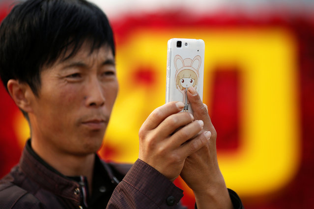 A man takes pictures of himself as people gather in Tiananmen Square to celebrate National Day marking the 67th anniversary of the founding of the People's Republic of China, in Beijing October 1, 2016. (Photo by Damir Sagolj/Reuters)