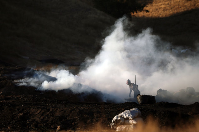 A wood charcoal worker is seen among smoke at Ugurlu village in Kizilcahamam district of Turkish capital Ankara on October 12, 2020. Wood charcoal production workers begin their works with the first lights of the day, where oak wood is converted into coal. (Photo by Mehmet Kaman/Anadolu Agency via Getty Images)