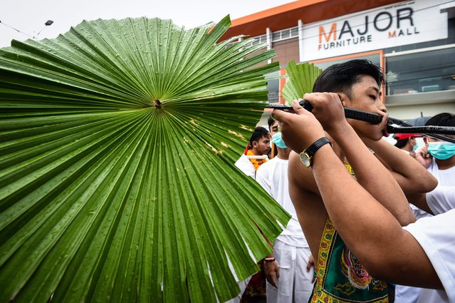 A devotee of the Nine Emperor Gods marches with palm leaves pierced through his cheeks during the annual Phuket Vegetarian Festival in the southern province of Phuket on October 1, 2016. (Photo by Lillian Suwanrumpha/AFP Photo)