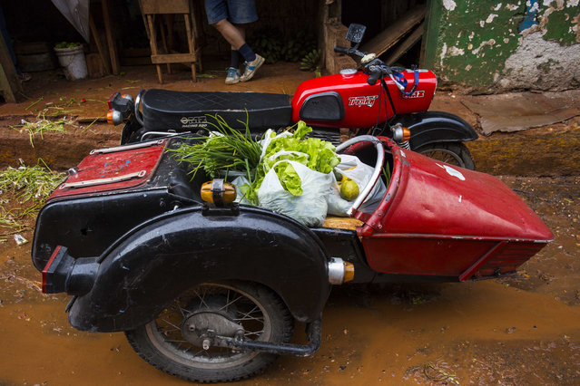 In this September 27, 2015, file photo, a former East German-made MZ motorcycle sidecar is filled with vegetables and stew ingredients at a market in Havana, Cuba. The sprouting of high-end clubs and bars around Havana is unsettling to many in Cuba who grew up believing in equality as a tenet of the revolution, and now see foreigners and wealthy Cubans spending many times in one night the roughly $30 monthly salary of the average Cuban state worker. (Photo by Desmond Boylan/AP Photo)