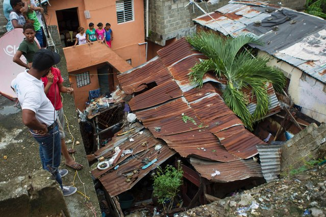 People look at the collapsed roof of a house where a child died in the neighbourhood of La Puya, in Santo Domingo on October 4, 2016 during the passage of Hurricane Matthew through Hispaniola – the island that the Dominican Republic shares with Haiti. (Photo by Erika Santelices/AFP Photo)