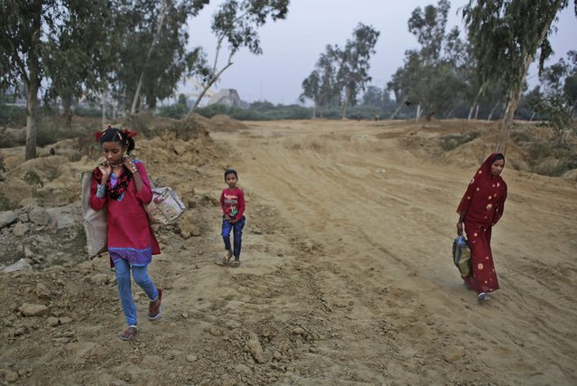 In this November 18, 2014 photo, Marjina, right, her daughter Murshida, 12, and seven-year old brother Shahid-ul make their way towards a train station on the outskirts of New Delhi, India. (Photo by Altaf Qadri/AP Photo)