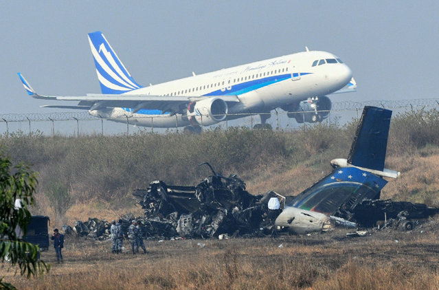 An airplane takes off at the international airport in Kathmandu on March 13, 2018, near the wreckage of a US- Bangla Airlines plane that crashed on March 12. At least 49 people were killed and 22 injured when a Bangladeshi plane crashed and burst into flames near Kathmandu airport on March 12, in the worst aviation disaster to hit Nepal in years. Officials said there were 71 people on board the US- Bangla Airlines plane from Dhaka when it crashed into a field near the airport. (Photo by Prakash Mathema/AFP Photo)