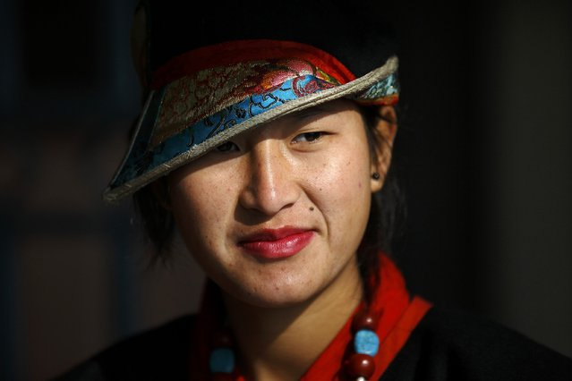 A Tibetan girl in traditional attire takes part in a function organised by the Tibetan Refugee Community in Nepal commemorating the 25th Anniversary of the Nobel Peace Prize conferment to exiled Tibetan spiritual leader Dalai Lama and the 66th International Human Rights Day in Kathmandu December 10, 2014. (Photo by Navesh Chitrakar/Reuters)