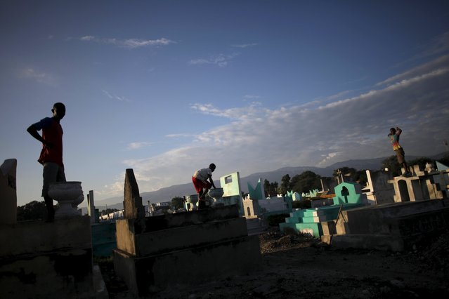 Kids stand on the top of tombs in the cemetery of Croix des Bouquets, in the outskirts of Port-au-Prince, Haiti, November 1, 2015. (Photo by Andres Martinez Casares/Reuters)
