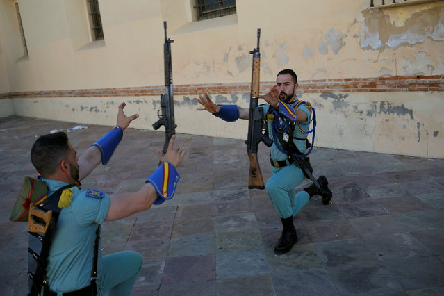 """Spanish legionnaires throw their weapons in the air as they warm up outside a church before taking part in a change of honor guard at the statue of the Christ of """"Mena"""" brotherhood during Holy Week in Malaga, southern Spain, March 26, 2018. (Photo by Jon Nazca/Reuters)"""