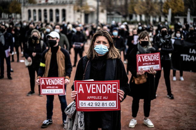 """Demonstrators hold a placard reading """"for sale"""" during a rally of shop owners calling for the reopening of their stores closed as part of measures taken by the government to close their establishments to curb the spread of the covid-19 pandemic on November 16, 2020 in Lyon. (Photo by Jeff Pachoud/AFP Photo)"""