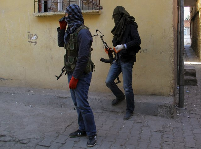 "Masked members of YDG-H, youth wing of the outlawed Kurdistan Workers Party (PKK), stand at a corner in Sur neighbourhood of the southeastern city of Diyarbakir, Turkey, November 6, 2015. Kurdish militants scrapped a month-old ceasefire in Turkey on Thursday, a day after President Tayyip Erdogan vowed to ""liquidate"" them, dashing hopes of any let-up in violence in the wake of a national election. (Photo by Sertac Kayar/Reuters)"