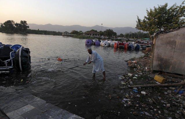 A man clears rubbish from the lake at the Rawal Lake Park in Islamabad, Pakistan, October 21, 2015. (Photo by Faisal Mahmood/Reuters)