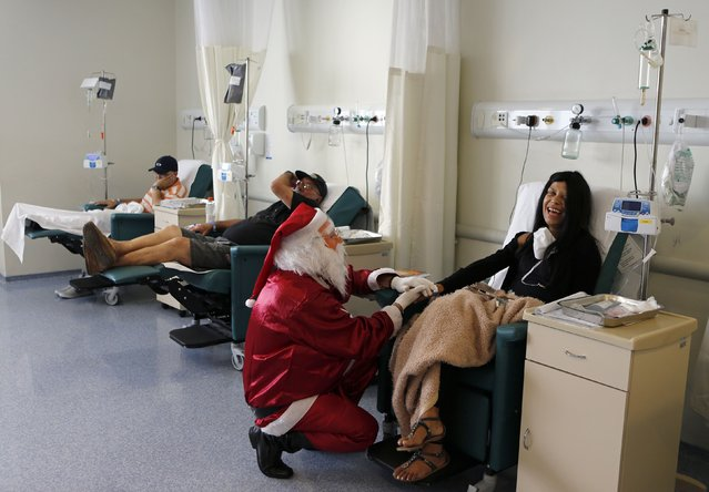A man dressed as Santa Claus talks to a cancer patient undergoing chemotherapy in the Cancer Institute in Sao Paulo December 19, 2014. (Photo by Paulo Whitaker/Reuters)