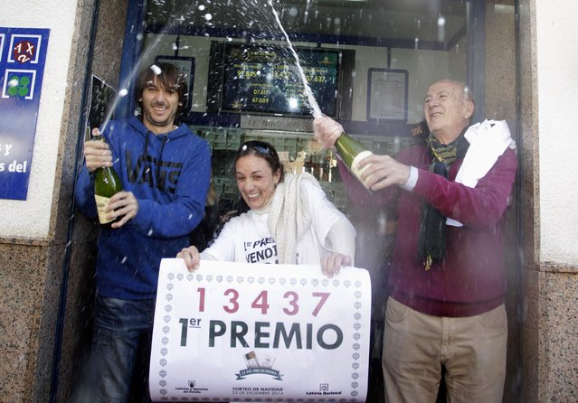 """Lottery seller Raquel Carrasco (C) holds a sign with the winning number of Spain's Christmas Lottery """"El Gordo"""", as employees spray champagne in La Eliana near Valencia December 22, 2014. (Photo by Heino Kalis/Reuters)"""