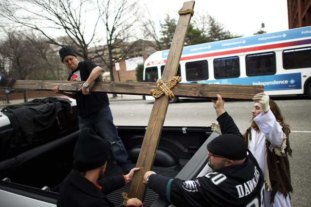 "Supporters (L-R) Jason Krieck, 38, Ryan Bolli, 42, and Nando Fuselli, 38, assist Michael Grant, 28, ""Philly Jesus"", in lashing the 12 foot cross to a truck following his 8 miles cross walk through North Philadelphia to Center City as part of a Christmas walk to spread the true message of the holiday in Philadelphia, Pennsylvania December 20, 2014. (Photo by Mark Makela/Reuters)"
