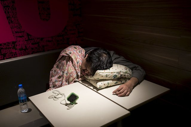 An alarm clock is seen on a table as a man sleeps on a pillow at a 24-hour McDonald's restaurant in Hong Kong, China November 11, 2015. (Photo by Tyrone Siu/Reuters)
