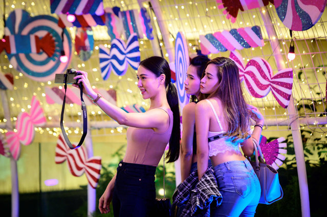 Young women pose for photos in a Christmas-themed tunnel lit-up with decorations outside a shopping mall in Bangkok on December 4, 2020. (Photo by Mladen Antonov/AFP Photo)