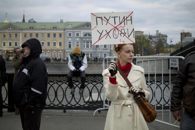 """A woman holds a poster reading """"Putin Go Away"""" during a protest rally in Bolotnaya Square in Moscow, Russia, Monday, May 6, 2013. Up to 20,000 Russian opposition supporters gathered for a protest on Monday, venting anger against the Kremlin and demanding the release of political prisoners. The protest came exactly one year after a demonstration a day before President Vladimir Putin's third presidential inauguration on the same square near the Kremlin ended in violent clashes between demonstrators and police. (AP Photo/Ivan Sekretarev)"""