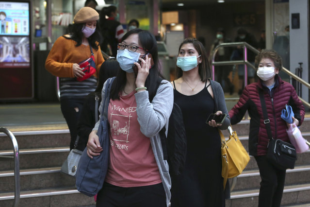People wearing face masks to protect against the spread of the coronavirus walk in Taipei, Taiwan, Tuesday, December 29, 2020. (Photo by Chiang Ying-ying/AP Photo)