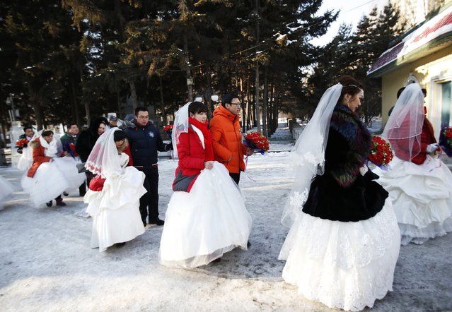 Newly-wed couples make their way after their group wedding ceremony which was held as part of the Harbin International Ice and Snow Festival in the northern city of Harbin, Heilongjiang province January 6, 2015. (Photo by Kim Kyung-Hoon/Reuters)
