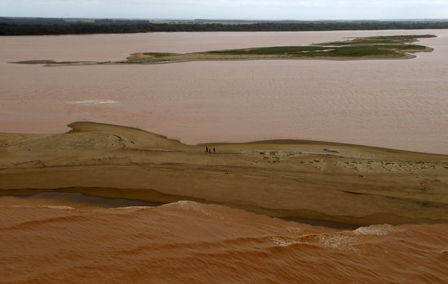 People walk between the sea (bottom) and the Rio Doce (Doce River), which was flooded with mud after a dam owned by Vale SA and BHP Billiton Ltd burst, as the river joins the sea on the coast of Espirito Santo in Povoacao Village, Brazil, November 22, 2015. (Photo by Ricardo Moraes/Reuters)
