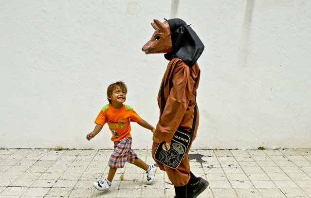 A boy playfully teases another boy dressed in a traditional devil mask and costume during Corpus Christi celebrations in the streets of La Villa, Panama, on May 30, 2013. (Photo by Arnulfo Franco/Associated Press)