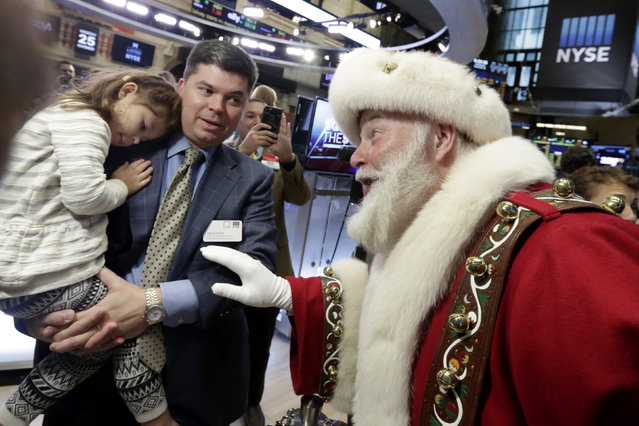 Piper Foley, 4, daughter of New York Stock Exchange Senior Vice President Douglas Foley, meets Santa Claus from the Macy's Thanksgiving Parade, on the floor of the New York Stock Exchange before the opening bell Wednesday, November 25, 2015. (Photo by Richard Drew/AP Photo)