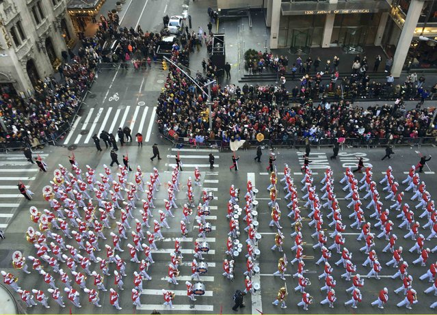 Spectators watch as a marching band proceeds along 6th Ave during the 89th Macy's Thanksgiving Day Parade in the Manhattan borough of New York November 26, 2015. (Photo by Carlo Allegri/Reuters)